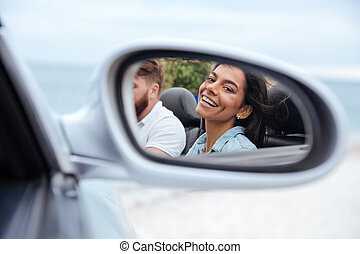 Beautiful woman looking at her reflection in a car mirror