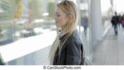 Beautiful woman looking at shop-window - Beautiful young...