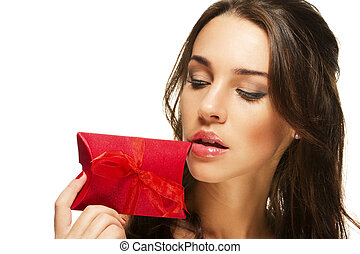 beautiful woman looking at the present near her face on white background