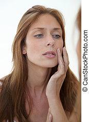Beautiful woman looking in a mirror