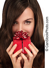 Beautiful woman looking in the camera holding a Christmas gift