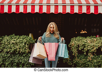 Beautiful woman looking in the shopping bag with excitement