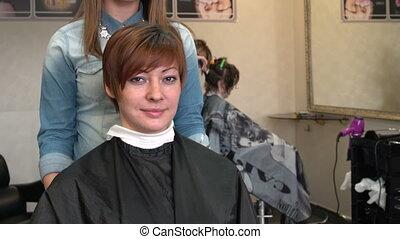 Beautiful woman looking into a mirror in beauty salon