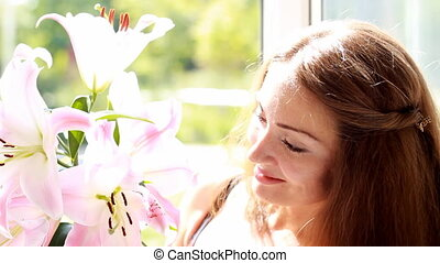 Beautiful woman looking on lily and sniffing scent of...