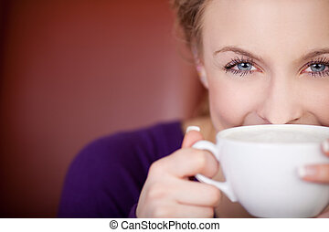 beautiful woman looking over a cup of coffee