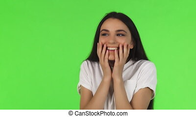 Beautiful woman looking surprised and excited on green...