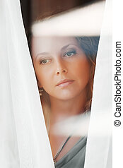Beautiful woman looking through a window.