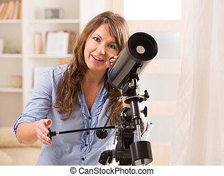 Beautiful woman looking through telescope