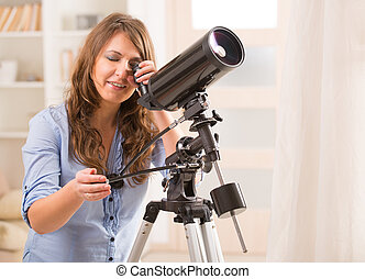 Beautiful woman looking through telescope