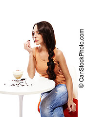 beautiful woman looking to a coffee bean in her hand sitting on a table with cappuccino coffee on white background