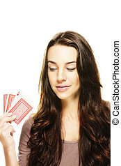 beautiful woman looking to the poker cards in her hand on white background