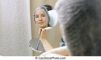 Beautiful woman looks at herself in mirror after cosmetic procedures in the beauty salon