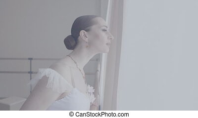 Beautiful woman looks out of the window