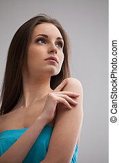 Beautiful woman. Low angle view of beautiful young woman in blue dress touching her shoulder and looking away while standing isolated on grey background