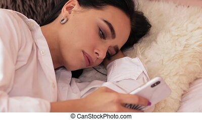 Beautiful woman lying in bed with a smartphone in slow motion