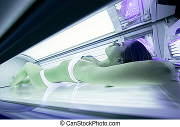 Beautiful woman lying in solarium