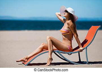 Beautiful woman lying on a deckchair at the beach