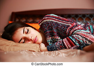 Beautiful woman lying on bed sleeping at home in the bedroom