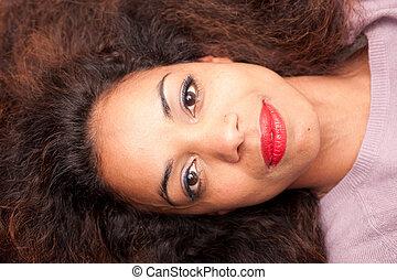 beautiful woman lying on her sofa looking at camera