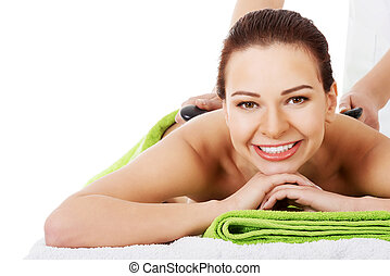 Beautiful woman lying on spa salon having stone massage.