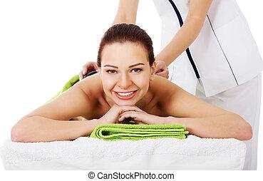 Beautiful woman lying on spa salon having stone massage.