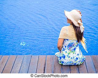 Beautiful woman lying on the edge of the swimming pool.