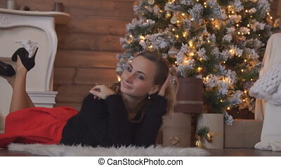 Beautiful woman lying on the floor by the Christmas tree