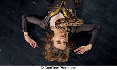 Beautiful woman lying on the floor with a snake dancing in a studio