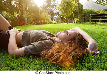 Beautiful woman lying outside listening to music