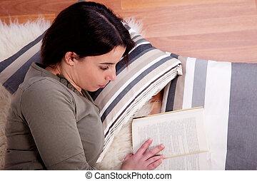 beautiful woman lying, reading a book