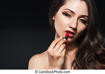 Beautiful woman makes makeup applying pink lipstick on lips.