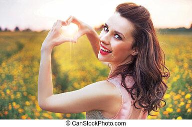 Beautiful woman making a heart sign - Beautiful lady making...
