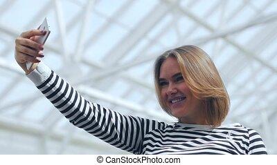 Beautiful woman making selfie in the mall.