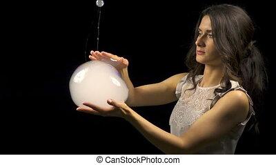 Beautiful woman making smoke soap bubbles on black...
