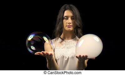 Beautiful woman making soap bubbles with smoke