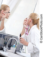 Beautiful woman mascaras her eyelashes in bathroom
