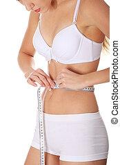 Beautiful woman measuring her perfect shape
