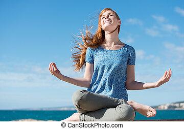Beautiful woman meditating at the seaside