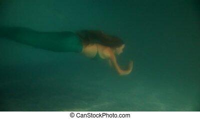 Beautiful woman mermaid diving and swimming underwater