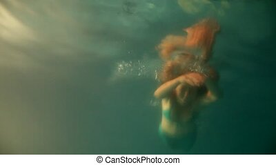 Beautiful woman mermaid diving  and swimming underwater