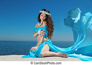 Beautiful woman model in Blowing Dress Flying resting over blue sky