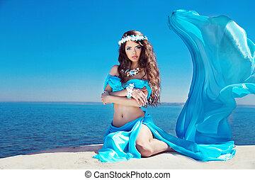 Beautiful woman model posing in blowing dress over blue sky
