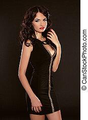 Beautiful woman model posing in elegant dress isolated on black background. Fashion Photo.