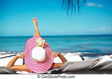Beautiful woman model sunbathing on the beach chair in white...