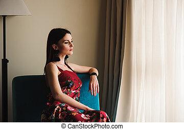 Beautiful woman near a window in a room