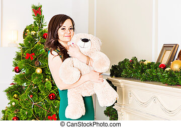 Beautiful woman near the Christmas tree with Teddy bear