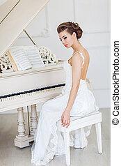 Beautiful woman near the white piano
