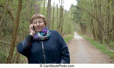 Beautiful woman of age, talking on the phone, smiling, happy with the good news. For a walk in the park.