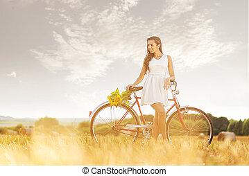 Beautiful woman old bicycle with flowers in wheat field