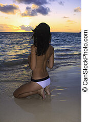 woman on a hawaii beach at sunrise